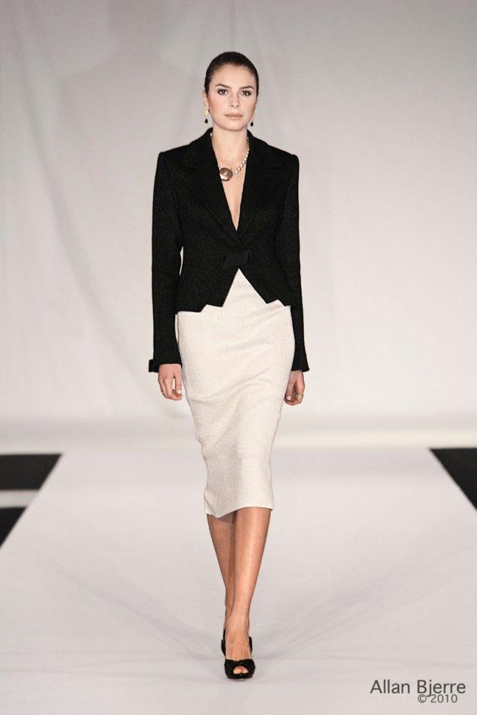 Sort jakke med bret rever, lukket med sløjfe, off-white nederdel med slids